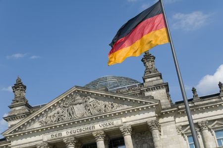The German flag flying in front of the Reichstag in Berlin. The phrase Dem Deutschen Volke (To the German people), designed by Peter Behrens, was added to the building in 1916.