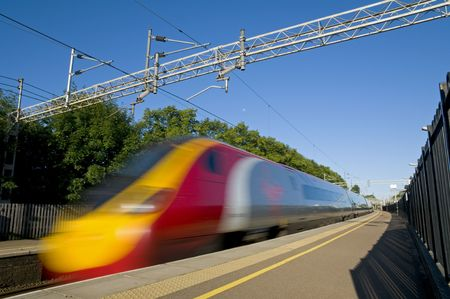 A British high speed passenger train passing through a station in the early morning. Editorial