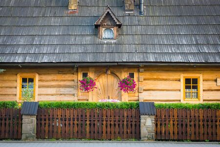 Wooden highlander house covered with shingle. Entrance door, flowers hanging at the entrance.