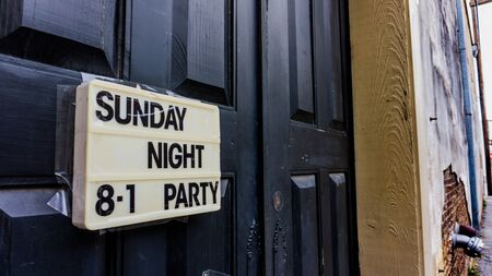 Black door in a back alleyway with a sign advertising a party