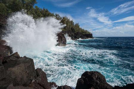 granola: A big wave breaks on a rocky shoreline Foto de archivo
