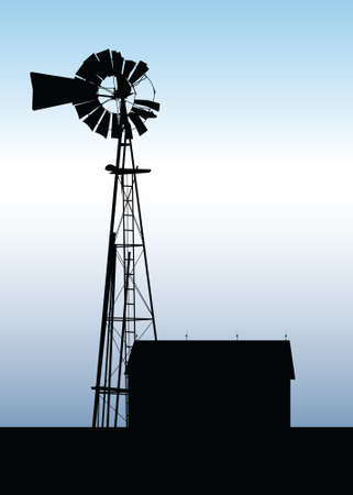 A silhouette of an old, unused farm windmill beside a barn.