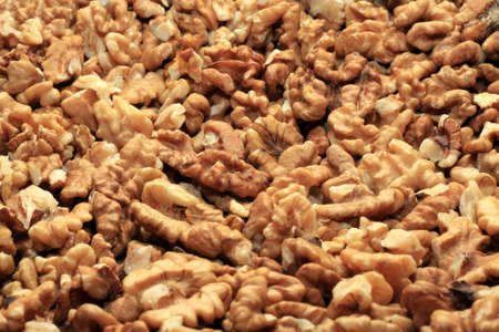 Cracked walnuts cores with more nuts as background photo