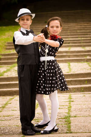 Portrait of a very young couple in retro garment posing at the camera.  Stock Photo