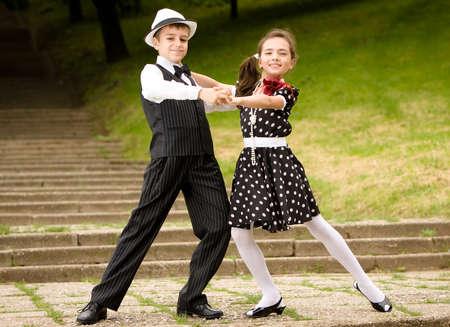 bailes de salsa: Retrato de una pareja muy joven en retro de prendas de vestir que presentan a la c�mara. M�s im�genes con los mismos modelos. Foto de archivo