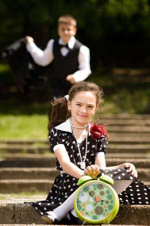 llegar tarde: Retrato de una joven muy esperando su compa�ero mientras el ni�o ejecut�ndose en segundo plano est� tratando de no llegar tarde. M�s im�genes con los mismos modelos. Foto de archivo