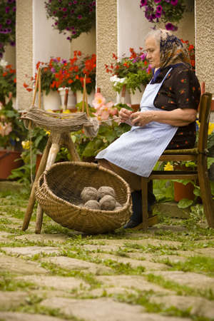 Portrait of a romanian very old woman in traditional clothing making kneel balls. See more images. photo