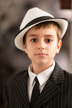 hair tie: Portrait on a lovely boy with attitude in a black tuxedo with shirt and tie. See other images. Stock Photo