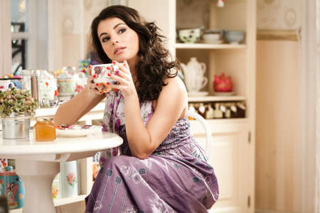 Lovely woman drinking her tea while is looking away