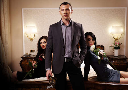 A man with a mask standing in front of two ladies. See more images from the same shoot. Stock Photo - 9800187
