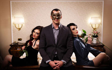 A man with a mask and two ladies with roses. See more images from the same shoot.