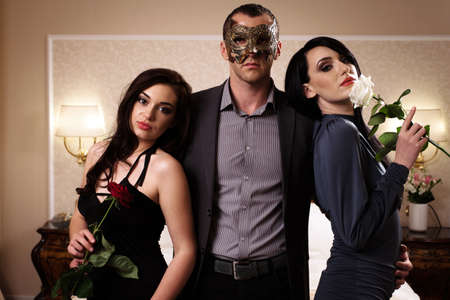 A man with a mask and two ladies with roses.  photo