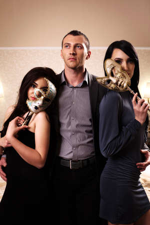 A man with two ladies wearing masks. See more images from the same shoot. photo