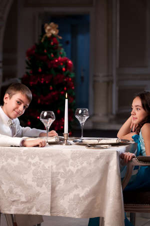 Lovely young couple having dinner in a romantic restaurant in Christmas time. Please see more images from the same shoot. photo