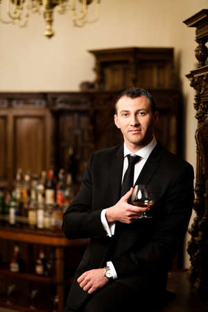 Attractive man in tuxedo having a glass of cognac. See more images from the same shoot. photo