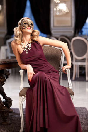 female mask: Sensual blonde with a mask, sitting in a ballroom. Please see more imeges from the same shoot. Stock Photo