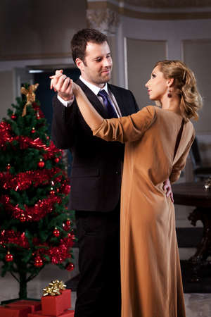 Lovely young couple dancing in a romantic restaurant in Christmas time. Please see more images from the same shoot.
