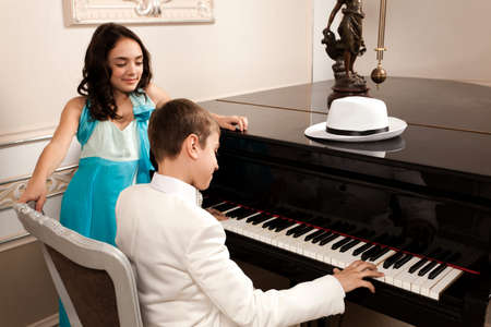 Lovely young lady admiring his boy performing at a grand piano. Please see more images from the same shoot. photo