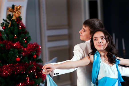 Very young couple dancing in a luxury restaurant at Christmas time. Please see more images from the same shoot. photo
