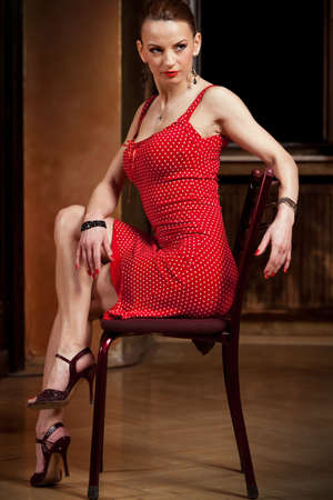Beautiful blond in a red dress looking away. Please see more images from the same shoot. photo