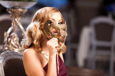 Belle blonde avec un masque dans une élégante robe rouge.