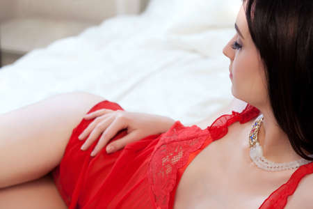 Young gorgeous brunette in sexy dress laying in a vintage style bed  Stock Photo - 13653539