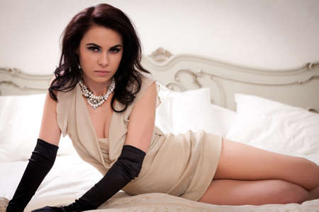 Young gorgeous brunette in sexy dress laying in a vintage style bed  Stock Photo
