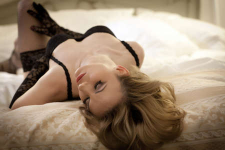 Young gorgeous blond woman in sexy lingerie posing in bed