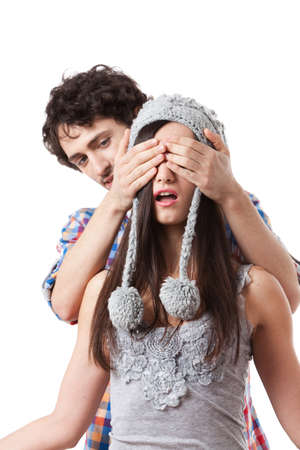 covering eyes: Lovely young couple having fun with a winter cap