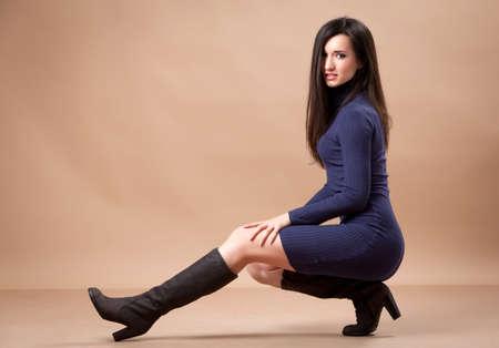 Mooi meisje zittend op de hielen, terwijl is op zoek naar camera Stockfoto