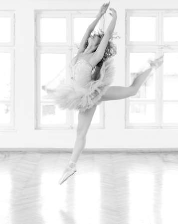 ballerina costume: Young, beautifull ballerina exercising in studio  A black and white image with grain added as effect