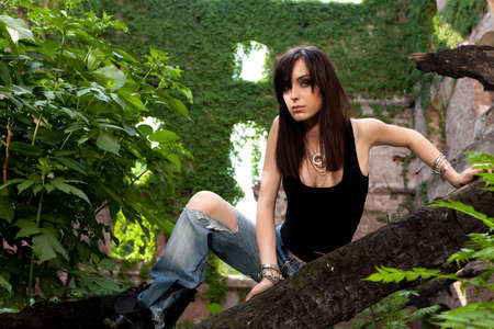Contrast between beautiful brunette and the green leaves and ivy surrounding her  Stock Photo - 19339785