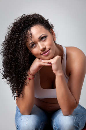 cute attitude: Pregnant caucasian woman with beautiful curly hair, sitting and leaning on her hands with a smily cute attitude