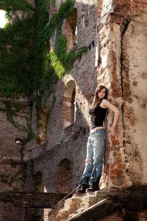 Beautiful woman with trendy style in torn jeans leaning to a brick wall  photo