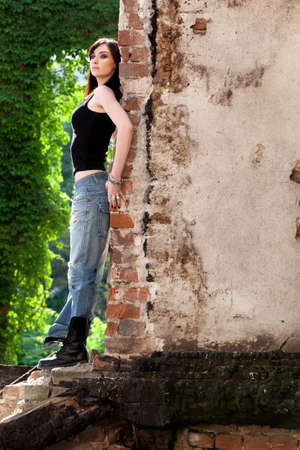 Brunette profile having a confident attitude leaning to a brick wall  Stock Photo - 20680477