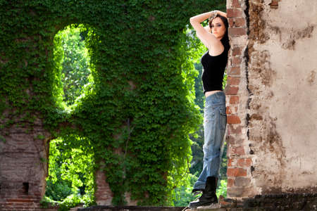 Brunette wearing torn jeans and black t-shirt, with daring attitude  photo
