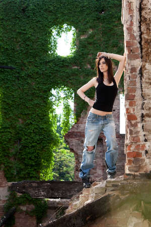 Beautiful and mysteus brunette with a strong active attitude with green ivy in the backround  Stock Photo - 20680851