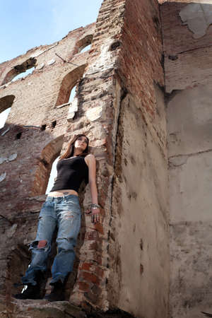 A sexy dangerous attitude, a beautiful woman hiding, leaning on to the wall in a deserted building  photo