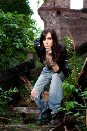 Beautiful brunette in torn jeans, opening widely her leather coat showing her sexy body, in a teasing attitude   photo