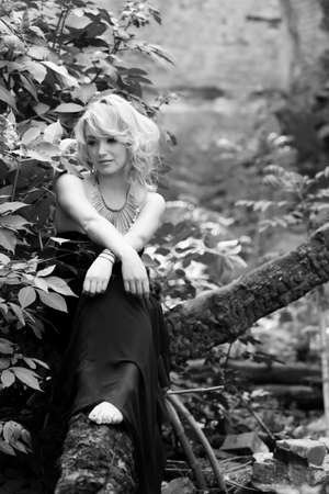 nostalgy: Photo in black and white  A gracious and delicate blonde woman in long black dress sitting pensively on a tree