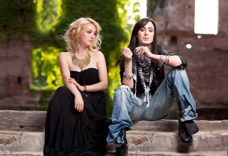 Strong contrast between very elegant and blonde woman sitting together with a daring brunette in torn jeans, lighting her cigarette   photo