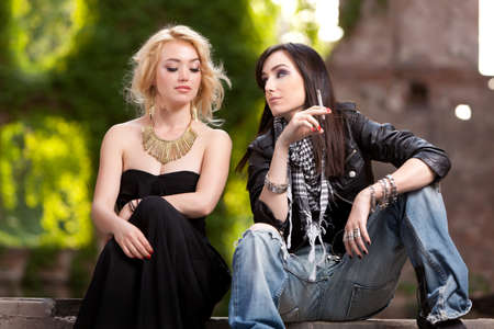 Two attractive gorgeous women with contrasting dressing styles measuring one another with slight fascination  photo