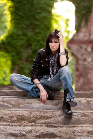 Nasty brunette in leather jacket and torn jeans sitting at leisure on some stairs  photo