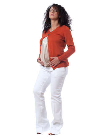 Pregnant caucasian woman with beautiful curly hair, sitting and leaning on her hands with a smily cute attitude. photo
