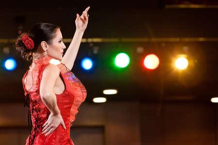 Sexy flamenco danseres haar dans in een rode lange jurk, arm omhoog Stockfoto