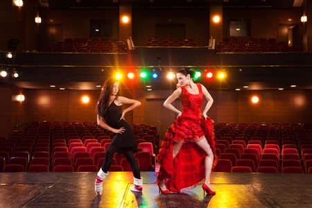 Two beautiful feminine dancers with different dance styles, performing a duet on stage