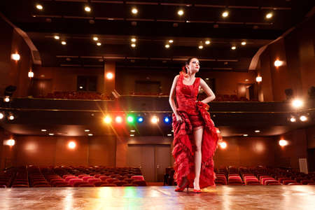 music hall: Sexy flamenco dancer performing her dance in a red long dress