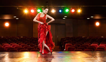 Sexy flamenco dancer performing her dance in a red long dress