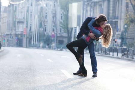 novios besandose: Pareja joven sonriendo y divertirse al aire libre en una fecha