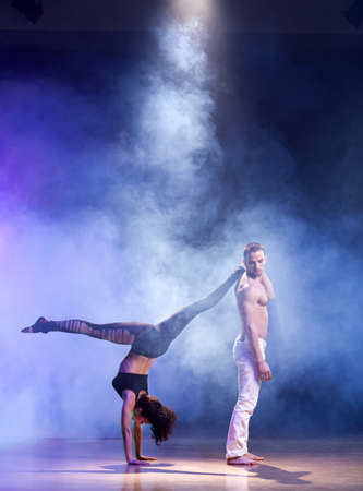 A man and a woman performing a contemporary dance pose on a stage  photo